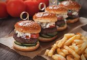 Mini hamburgers with french fries served as appetizer on wooden table