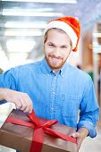 Young smiling man in Santa cap looking at camera while unpacking Christmas present