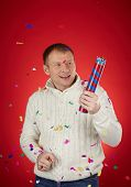 Joyful man in white knitted sweater holding confetti cracker