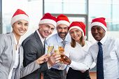 Group of successful business partners in Santa caps toasting with champagne and looking at camera