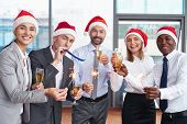 stock photo of office party  - Group of successful colleagues in Santa caps having Christmas party in office - JPG