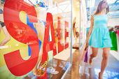 Word �?�¢??sale�?�¢?? on shop window and female shopper with paperbags walking on background