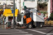 VALENCIA, SPAIN - NOVEMBER 16, 2014: A mechanical street sweeper in downtown Valencia. The very first street sweeping machine was patented in 1849 by its inventor, C.S. Bishop.