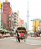 TOKYO, JAPAN-OCT 27,2014: Jinrikisha driven by an unidentified driver carrying two Japanese tourists in Tokyo,Japan.The word jinrikisha is of Japanese origin and means human-powered vehicle.