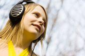 Blond woman listening music in headphones