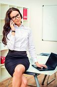 Modern businesswoman talking on her cellphone in the office.
