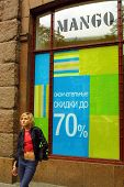 KIEV, UKRAINE, 16 AUGUST 2003: A young woman stands outside a Mango clothing store adverising a seasonal discount sale.  Punto Fa, S.L., trading as MANGO, is a Barcelona based clothing company.