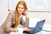 Young businesswoman working in the office with a laptop.
