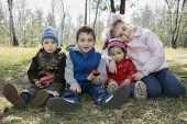Children Sit On The Grass In The Forest In The Spring.