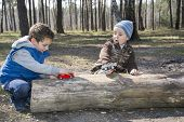 In The Forest, Sitting On A Log, Two Boys, One Playing With A Toy, Another Closely Watched.