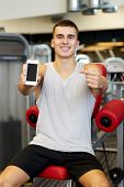 sport, bodybuilding, lifestyle, technology and people concept - smiling young man pointing finger to smartphone blank screen in gym