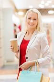 sale, consumerism and people concept - happy young woman with shopping bags and coffee paper cup in mall
