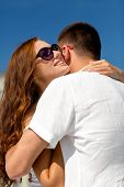 love, wedding, summer, dating and people concept - smiling couple wearing sunglasses hugging in city