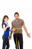 beautiful girl holding measuing tape around handsome muscular man