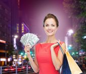 sale, money, people and holidays concept - smiling woman in red dress with shopping bags and dollars over city background