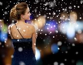 people, christmas, holidays and glamour concept - smiling woman in evening dress over black background over night lights and snow background from back