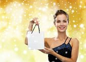 people, advertisement, christmas holydays and sale concept - smiling woman with white blank shopping bag over yellow lights and snow background