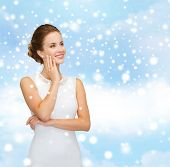 christmas, holidays, celebration, wedding and people concept - smiling woman in white dress wearing diamond ring over blue cloudy sky and snow background