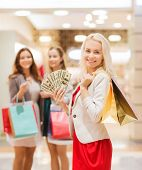 sale, consumerism and people concept - happy young women with shopping bags and usa dollar cash money in mall