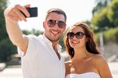 love, wedding, summer, dating and people concept - smiling couple wearing sunglasses hugging and making selfie with smartphone in park