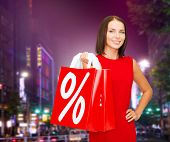 people, gifts, christmas and holidays concept - smiling young woman in red dress holding shopping bags with percent and sale sign over night city background