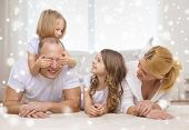 family, childhood, people and home concept - smiling parents with two little girls having fun at home