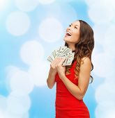 christmas, holidays, sale, banking and people concept - smiling woman in red dress with us dollar money over blue lights background
