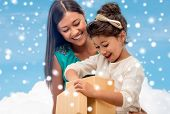 christmas, holidays, family and people concept - happy mother and child girl with gift box over blue snowy sky with cloud background
