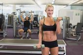 Portrait of a woman exercising with dumbbells in the gym