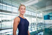 Portrait of a smiling female swimmer by the pool at leisure center