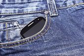 Mobile phone in the pocket of blue jeans