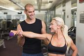 Smiling male trainer assisting woman with dumbbell in the gym