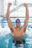Portrait of a fit swimmer cheering in the pool at leisure center