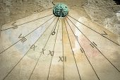 image of sundial  - Large decorative sundial catches the sunshine on side of building - JPG