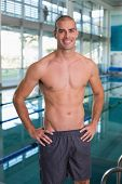 Portrait of a fit swimmer by the pool at leisure center