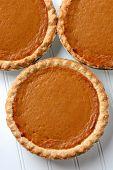 High angle closeup of three fresh baked pumpkin pies. The traditional American dessert - Pumpkin, pie is a Thanksgiving staple. Vertical format.