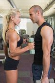Side view of a couple exercising with dumbbells in the gym