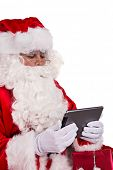 Photo of Santa Claus with tablet on white background.