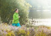 Young brunette woman running in autumn park.