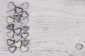 Shabby chic grey wooden background with a collection of hearts on the frame.