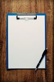 Blank Clipboard And Pen On A Wooden Desk