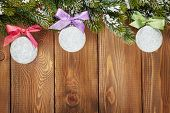 Christmas fir tree and baubles with colorful ribbon on rustic wooden board with copy space