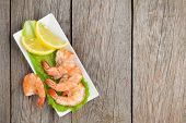 Cooked shrimps with lemon and salad leaves. View from above on wooden table with copy space