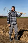 Portrait Of A European Farmer With A Pitchfork