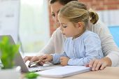 Mother working at home-office with daughter on her lap