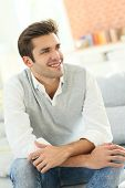 Portrait of smiling casual guy sitting in sofa