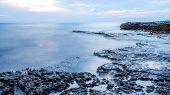 Rocky Seashore And Calm Blue Ocean