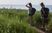 Two ladies hikers standing on the green meadow with lush grass