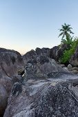 Close up Old Huge Rocks with Palm Tree Afar on Light Blue Sky Background. Located at Mahe Island, Seychelles.