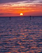 stock photo of gulf mexico  - Sun setting over the horizon and the Gulf of Mexico in Destin Florida - JPG
